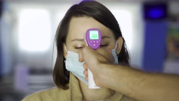 Operator checks fever by digital thermometer