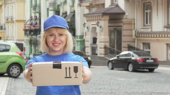 Thumbnail for Cheerful Delivery Woman in Blue Uniform Holding Cardboard Box