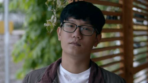 Portrait Young Man Asian in Glasses a Teenager Looks at the Camera. Teenage Man Wearing Glasses