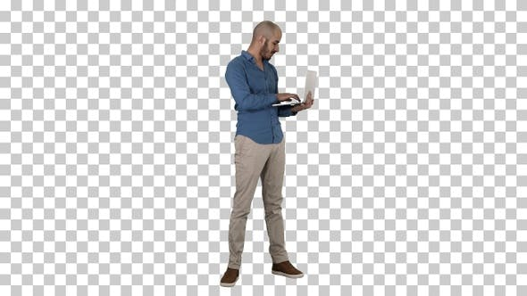 Thumbnail for Young middle eastern businessman standing and typing on laptop