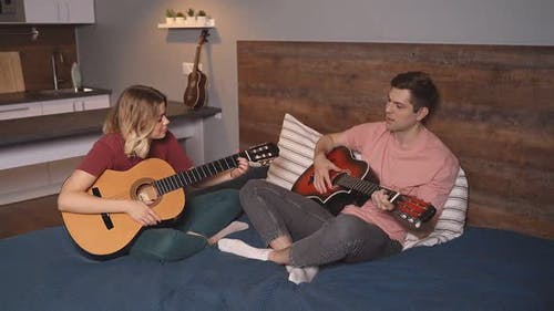 Cute Young Couple, Young People Play Guitar Together at Home, Sitting on the Bed. A Caucasian Girl
