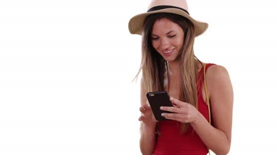 Glückliche Millennial Frau in Hut und Tank Top mit Telefon-app auf weißen Kopierraum