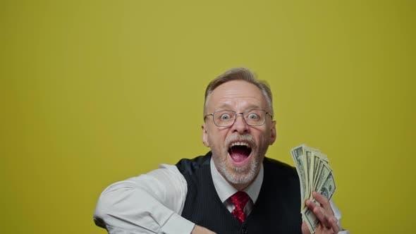 Thumbnail for Happy elderly man throwing money