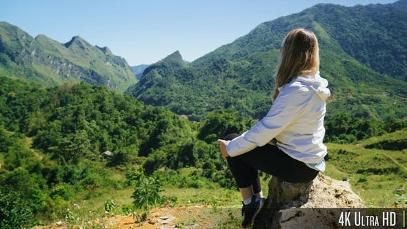 Thumbnail for 4K Rear View of a Young Woman Sitting on a Mountain Top
