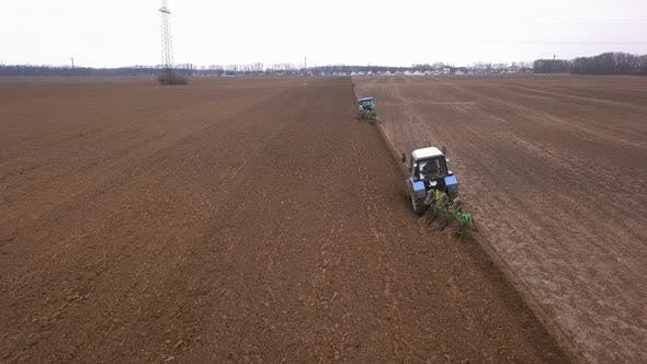 Agricultural Work in the Field, Two Blue Tractors Plow the Land