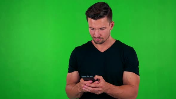 Thumbnail for Young Handsome Caucasian Man Works (Typing) on Smartphone - Green Screen
