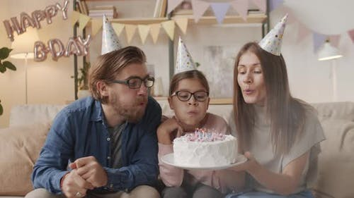 Cheerful Young Family Blowing Out Candles