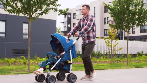 Father with Baby in Stroller Walking Along City