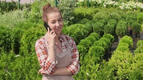 Female Gardener Talking On Phone In Yard
