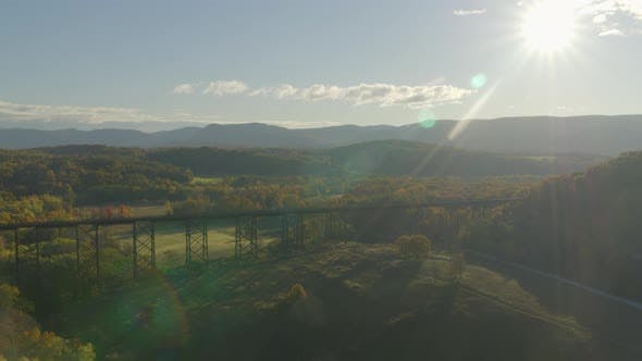 Aerial of sunlight falling on green valley landscape and railroad bridge