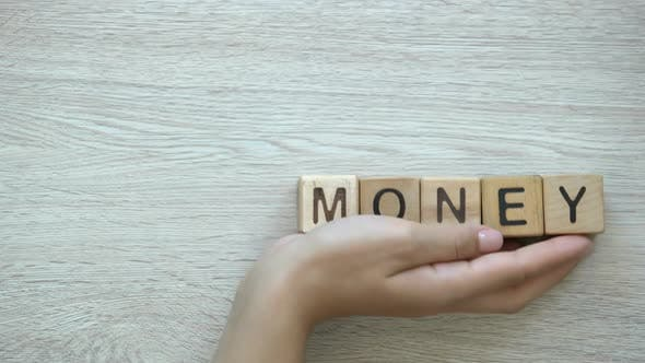 Thumbnail for No Money, Hand Pushing Words on Wooden Cubes, in Material Need, Loss and Damage