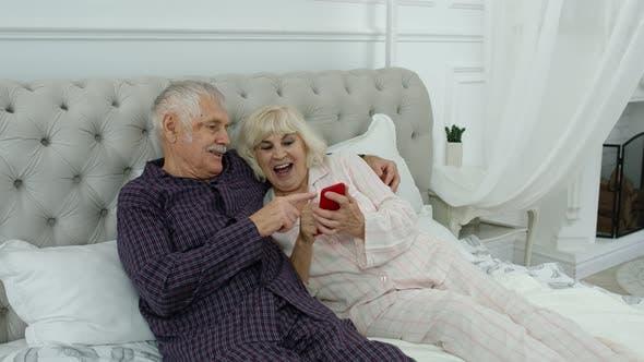 Thumbnail for Senior Elderly Couple Wearing Pyjamas Lying on Bed Looking on Mobile Phone Making Online Shopping