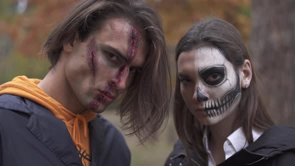 Thumbnail for Tall Handsome Man with Big Wound on His Face and Pretty Girl with Skull Makeup Standing Near, Both