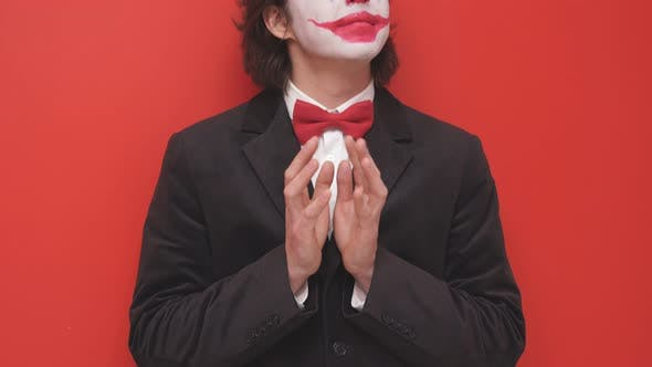 A Clown with Colorful Makeup Poses on an Isolated Red Background a Joyful Magician or a Mysterious