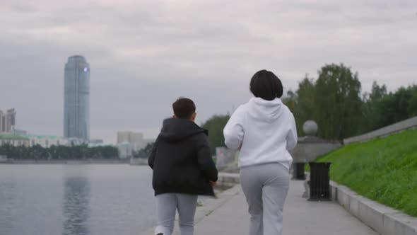 Thumbnail for Mother and Son Running Along Riverside in the Morning