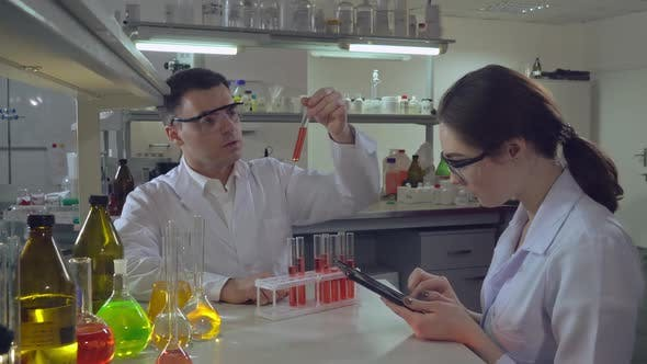 Thumbnail for Chemist Engineer Holding Test Tube with Liquid Talking with Student