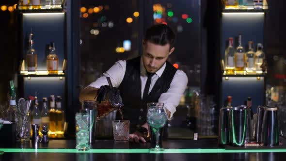 Thumbnail for Barman Pouring Cocktail To Glass in Bar