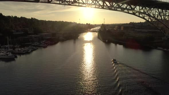 Thumbnail for Pulling Back Aerial Of Boat In Canal With Sun Ray Flashing Between City Bridge Rafters