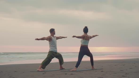 People Practicing Yoga Asanas on Beach