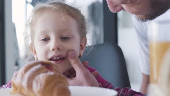 Thumbnail for Unerkennbarer Vater wischen Gesicht von niedlichen kleinen Mädchen Kauen Croissants. Aufmerksame junge Kaukasier