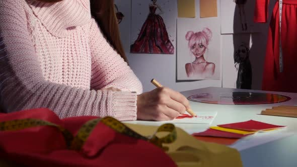Thumbnail for Hands Designer Draws a Sketch of a Dress, on a Cloth Table, for Tailoring