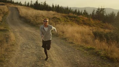 Strong Athlete Jogging on Dirty Road