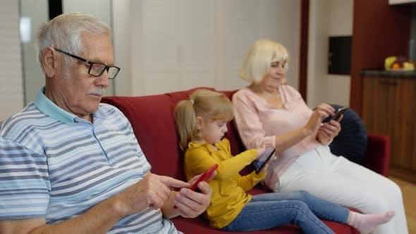 Thumbnail for Senior Couple Grandparents with Child Girl Granddaughter Using Digital Tablet, Mobile Phone