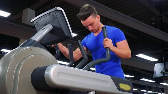 Thumbnail for A Young Fit Man Trains on an Elliptical Trainer in a Gym - Closeup From the Floor