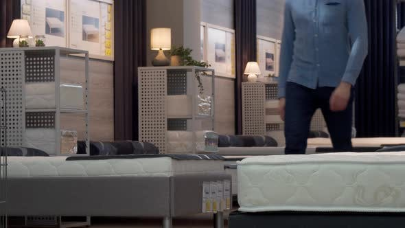 Thumbnail for Male Customer Choosing Orthopedic Mattress and Bed at Furniture Store