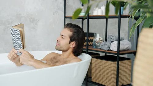 Smart Mixed Race Man Enjoying Book Reading Story in Bathtub Relaxing and Stydying in Bathroom