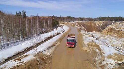 A lorry rides along on a dirt road the edge of a quarry 01