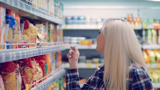 Woman Reads the Label on the Package at the Supermarket