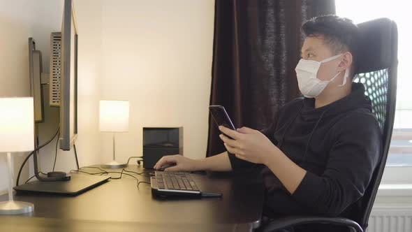 Thumbnail for A Young Asian Man in a Face Mask Works on a Desktop Computer and a Smartphone at Home