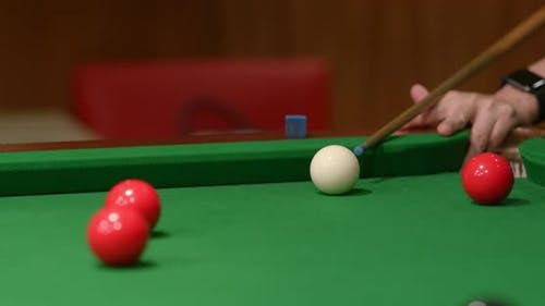 Striking snooker ball on table