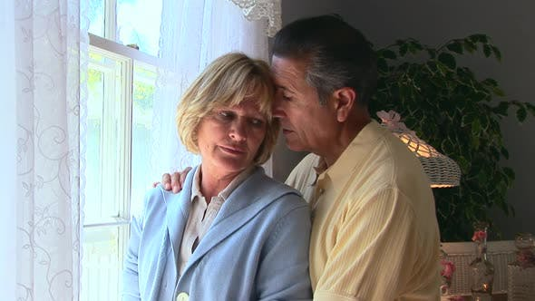 Thumbnail for Portrait of mature woman being consoled by husband