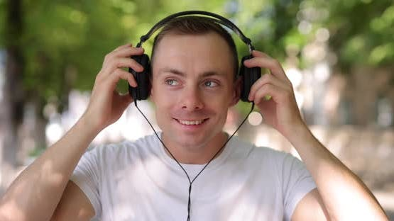 Smiling Man Puts on Big Headphones in the Summer City