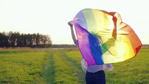 Young Woman Runs Across Field with LGBT Flag Slow Mo Rear View