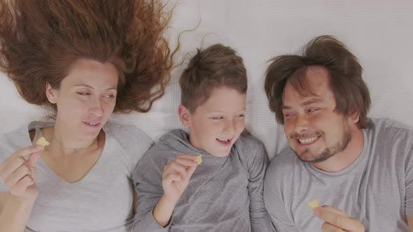 Thumbnail for Glückliche Familie Erwachsene Eltern Mama Papa und Cute Little Boy Fernsehen Zusammen Essen Snack Genießen
