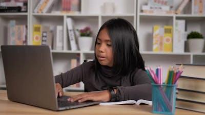 Girl learning online via laptop