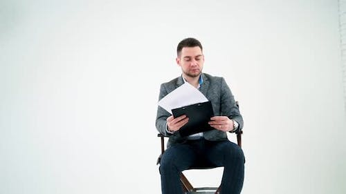 Serious businessman holding a folder and reading documents