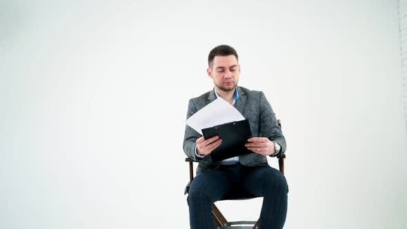 Thumbnail for Serious businessman holding a folder and reading documents