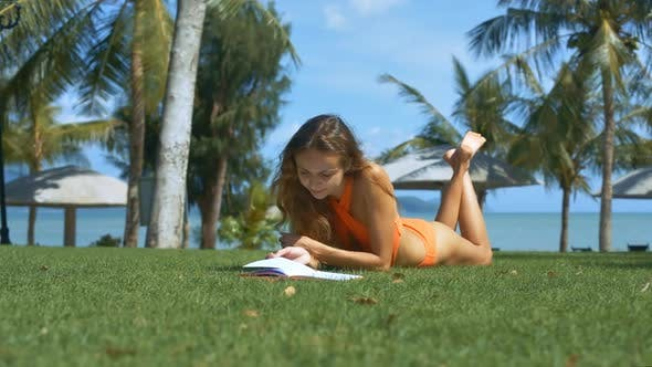 Thumbnail for Blonde Girl in Orange Swimsuit Reads on Green Lawn
