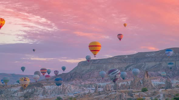 Colorful hot air balloons flying over rock landscape at Goreme, Cappadocia, Turkey. Timelapse 4K