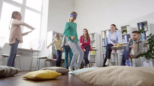 Blindfolded Teenager Carefully Edging around Cushions with Directions