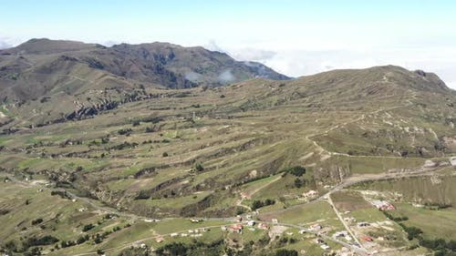 Aerial view that slowly flies over an agricultural landscape up in the andean mountains