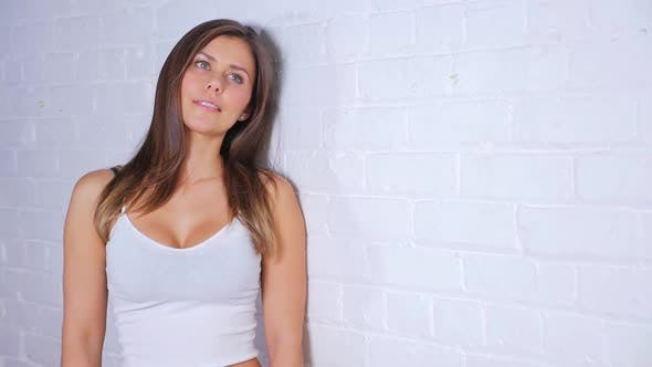 Thumbnail for Young Attractive Female Doing Different Poses While Smiling And Leaning Against A White Brick Wall 2