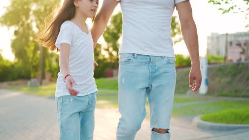 Dad and Daughter Walk Around Their Area at Sunset