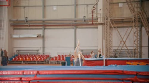 Pole Vaulting - Beautiful Athlete Is Running and Jumping Over the Bar