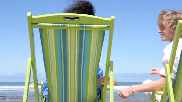 Thumbnail for Couple sitting in chairs at beach kiss