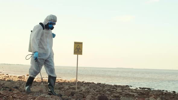 Ecologist Spraying Pesticides on Polluted Territory